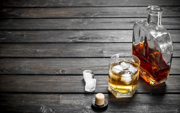 Whisky in een glazen fles en een glas. op houten