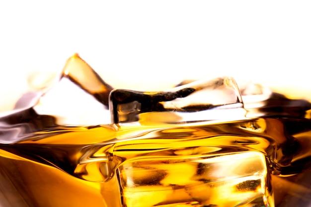 Whisky in glas met ijsblokje. op de rots