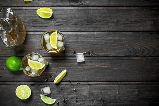 Whisky in glazen en een fles limoenplakken. op zwarte houten tafel