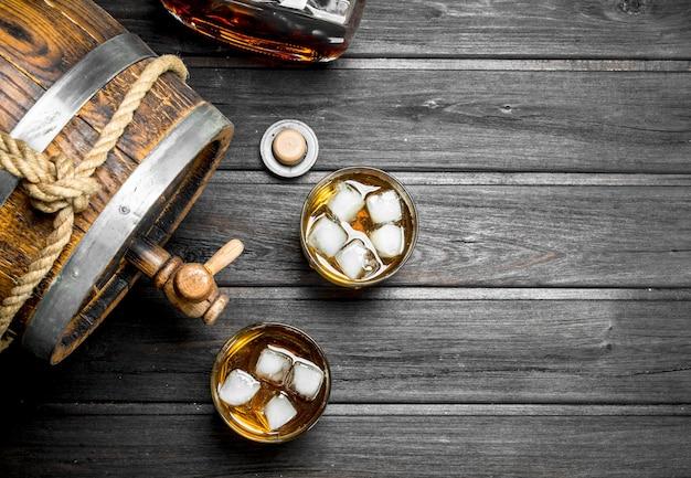 Whisky in glazen en vat. op zwarte houten tafel