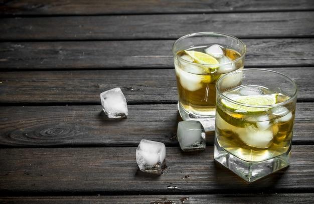 Whisky in glazen met ijs en limoenplakken.