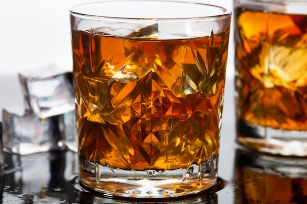Whisky in ouderwetse glazen met ijs, close-up