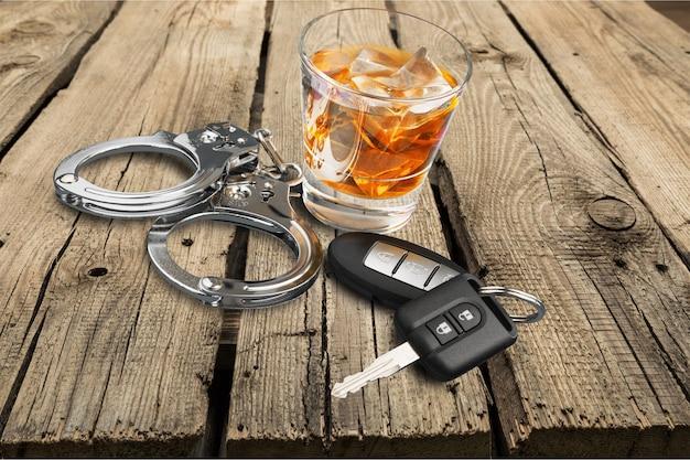 Whisky met autosleutels en handboeien concept voor drinken en rijden