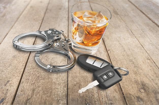 Whisky met autosleutels en handboeienconcept voor drinken en rijden