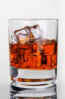 Whisky met ijs in glazen beker aan