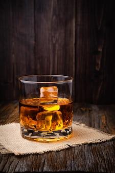 Whisky met ijsblokje in een bril op een rustieke donkere houten tafel