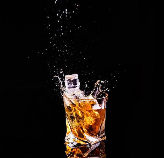 Whisky met splash op zwarte achtergrond, brandewijn in een glas