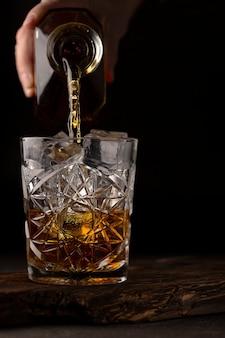 Whisky of cognac wordt in een ouderwets glas gegoten