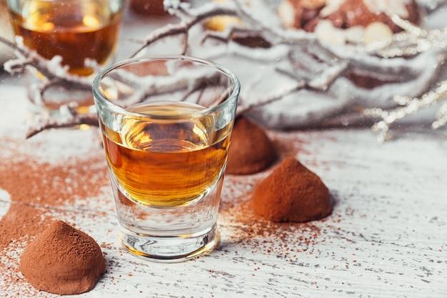 Whisky of likeur, truffel chocolade snoepjes in cacaopoeder en kerstversiering op witte houten achtergrond.