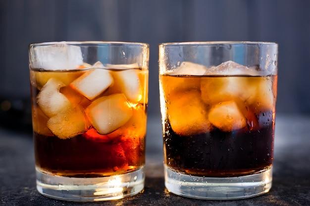 Whisky of rum met cola en ijs in glazen op een donkere achtergrond