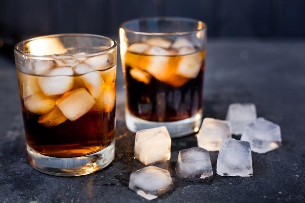 Whisky of rum met cola in glazen op een donkere achtergrond en ijs