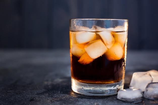 Whisky of rum met cola met ijs in een glas op een donkere achtergrond