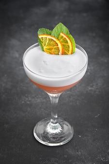 Whisky zure cocktail in een glas op een zwarte achtergrond