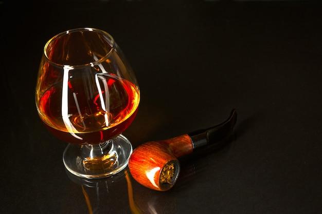 Whiskyglas en rokende pijp op zwarte achtergrond