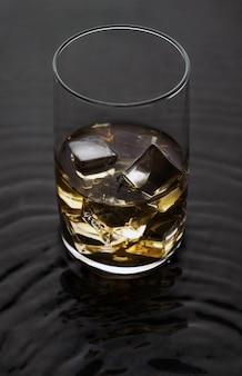 Whiskyglas met ijs op golvende vloeibare oppervlakte. alcoholische drank met ijsblokjes op water