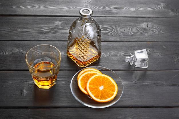 Whiskyglas met oranje fruit dat op donkere houten wordt gesneden