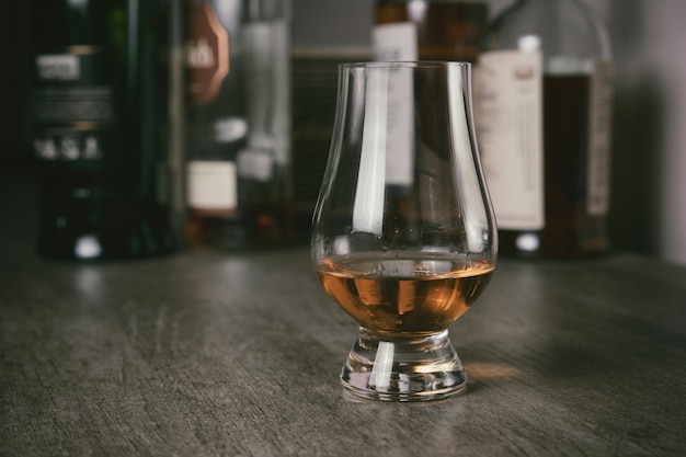 Whiskyglas met single malt whisky op houten tafel en whiskyflessen