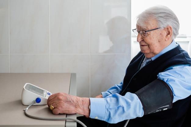 White-haired oudere man met bril zit een keukentafel zijn bloeddrukmeting te controleren