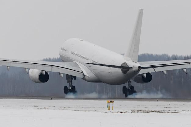 Wide-body vliegtuig landing op baan met rook van chassis, wintertijd