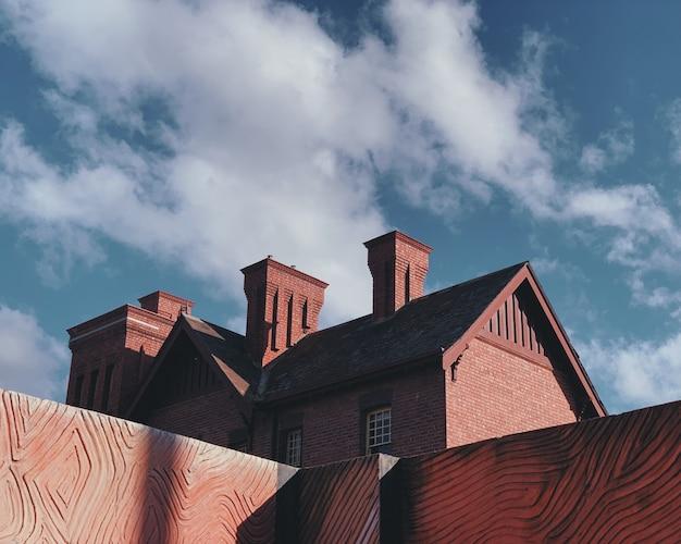 Wide shot van bruin gebouw onder witte wolken en blauwe hemel overdag