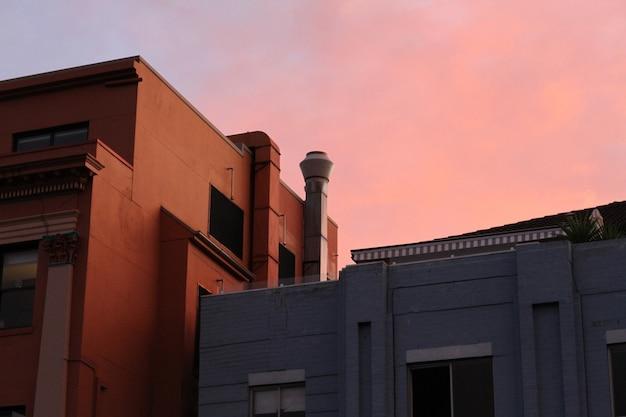 Wide shot van bruine en grijze huizen onder een roze hemel