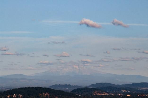 Wide shot van een berg omgeven door bossen van bomen onder een bewolkte blauwe hemel