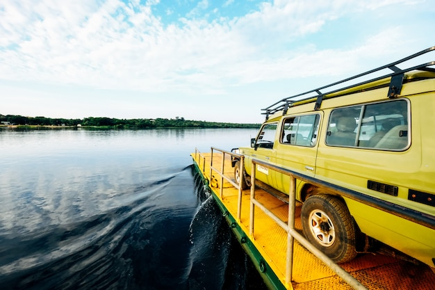 Wide shot van een gele busje op een gele dok aan zee onder een heldere hemel met wolken