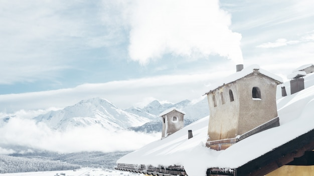 Wide shot van een huis in de buurt van bergen bedekt met sneeuw