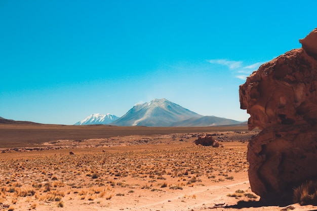 Wide shot van een klif en een berg in de woestijn met een heldere blauwe lucht op een zonnige dag