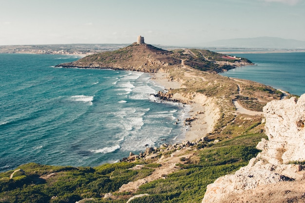 Wide shot van een klif en een heuvel aan zee