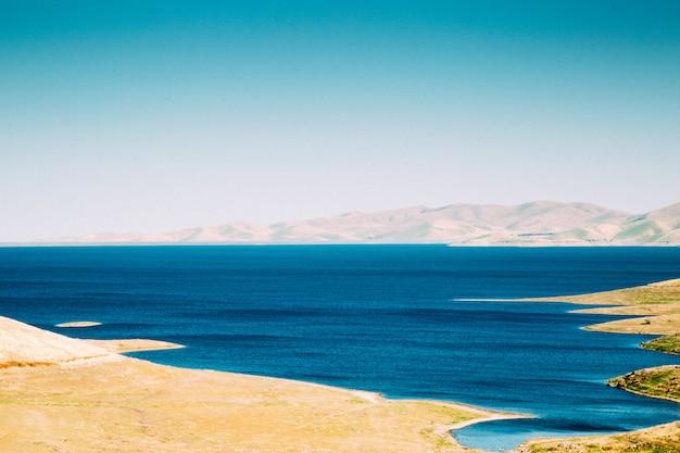 Wide shot van een oceaan met zandige kust van witte bergen onder een heldere hemel