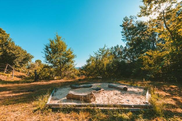 Wide shot van een park met een vuurkorf in een zandbak omgeven door planten en bomen