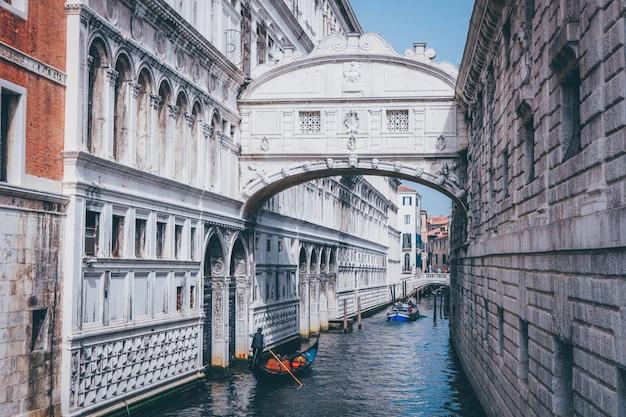 Wide shot van een persoon die een gondel op een rivier onder de brug der zuchten in venetië, italië roeien