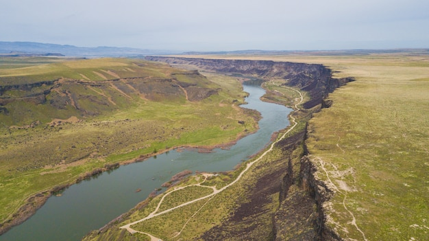 Wide shot van een rivier stroomt tussen groene heuvels onder een heldere hemel