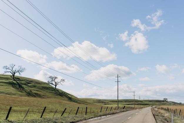 Wide shot van een snelweg weg in de buurt van groene heuvels onder een heldere blauwe hemel met wolken
