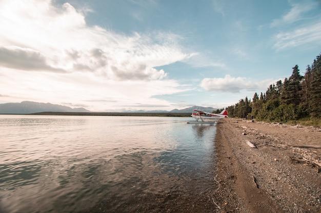 Wide shot van een watervliegtuig aan de kust in de buurt van een bos onder een heldere hemel met witte wolken