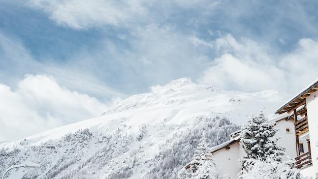 Wide shot van een wit en bruin huis in de buurt van bomen en een berg bedekt met sneeuw