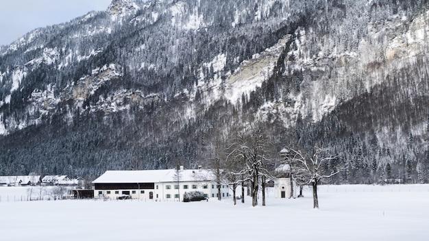 Wide shot van een wit huis omgeven door bomen en bergen bedekt met sneeuw