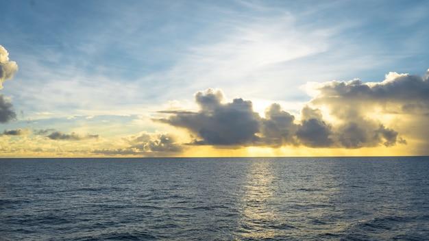 Wide shot van een zee en een bewolkte hemel bij onbeleefde zon
