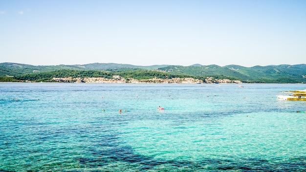 Wide shot van een zee met gebouwen aan de kust en beboste bergen in de verte