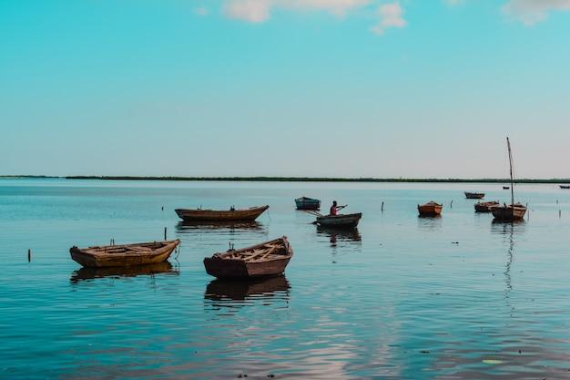 Wide shot van houten kleine boten in het water met een afro-amerikaanse persoon in een van hen