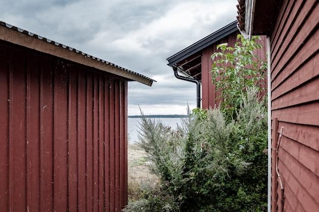 Wide shot van rode metalen kleine huizen aan de kust van de zee