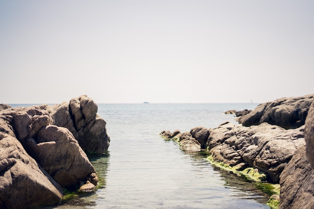 Wide shot van rotsformaties op het water onder een heldere hemel