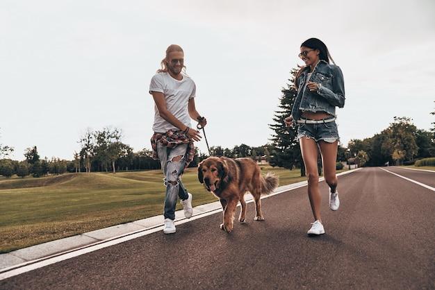 Wie gaat er als eerste komen? volledige lengte van een mooi jong stel dat met hun hond rent terwijl ze tijd buitenshuis doorbrengen