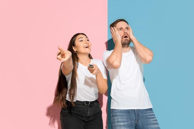 Wie heeft de touwtjes in handen. zij kiest tv-zender, hij is boos. jonge man, vrouw in casual op roze, blauwe tweekleurige muur. concept van menselijke emoties, gezichtsuitdrukking, relaties, advertentie. mooi koppel.