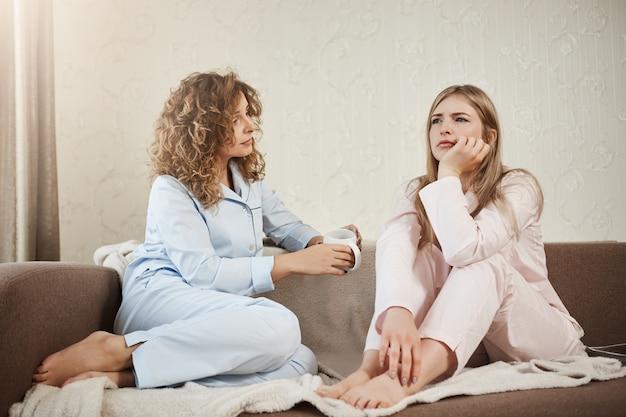 Wie heeft psycholoog nodig als je beste vriend hebt. twee vrouwen zitten op de sofa in nachtkleding in gezellige kamer, bespreken persoonlijke problemen, gericht en lastig gevallen met probleem. meisje probeert vriendin te troosten