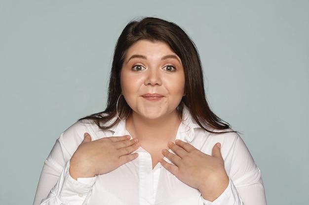 Wie ik. je bedoelt mij. aantrekkelijke nette jonge mollige vrouw draagt een wit formeel overhemd hand in hand op haar borst, verbaasd blij gelaatsuitdrukking, blij uitverkoren te zijn