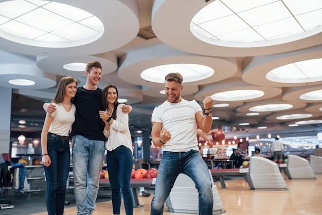 Wie is de winnaar. jonge, vrolijke vrienden vermaken zich in het weekend in de bowlingclub
