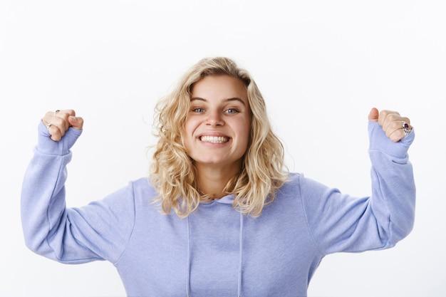 Wie is kampioen. portret van actieve en enthousiaste gelukkige knappe jonge vriendin met kort kapsel en blauwe ogen in paarse hoodie die handen opheft in viering en triomf vrolijk glimlachend