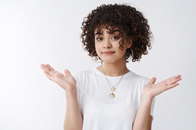 Wie kan het schelen. onbewust ontspannen stijlvolle verleidelijke jonge krullend-haired vrouwelijke clueless schouderophalend handen spreiden zijwaarts grijnzende kan het niet helpen geen idee, sorry weet niet gebaar, witte achtergrond